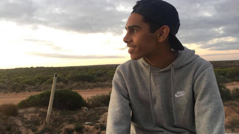 Young Aboriginal man wearing a grey hoody and cap looks out over bush landscape with cloudy sky in the background.
