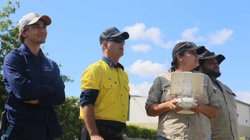 Three men and one woman dressed in work wear or casual wear stand shoulder to shoulder. The woman holds a white drone controller. All are looking up into the sky.