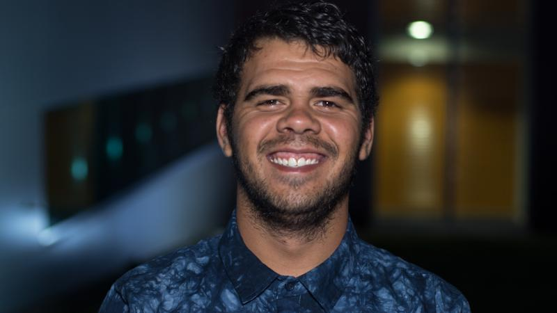 Aboriginal young man dressed in blue shirt. In the background is a light and doorway and some blue colours.