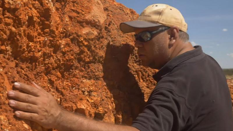 Aboriginal man in dark polo shirt, cap and sunglasses leans close to an ochre coloured rocky.