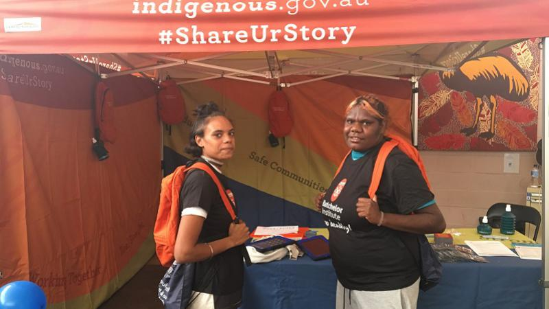 Two young Indigenous women wearing orange backpacks and dressed in Batchelor Institute shirts stand in front of a blue table topped with papers and pamphlets set up in a stall displaying the words: indigenous.gov.au #ShareUrStory.