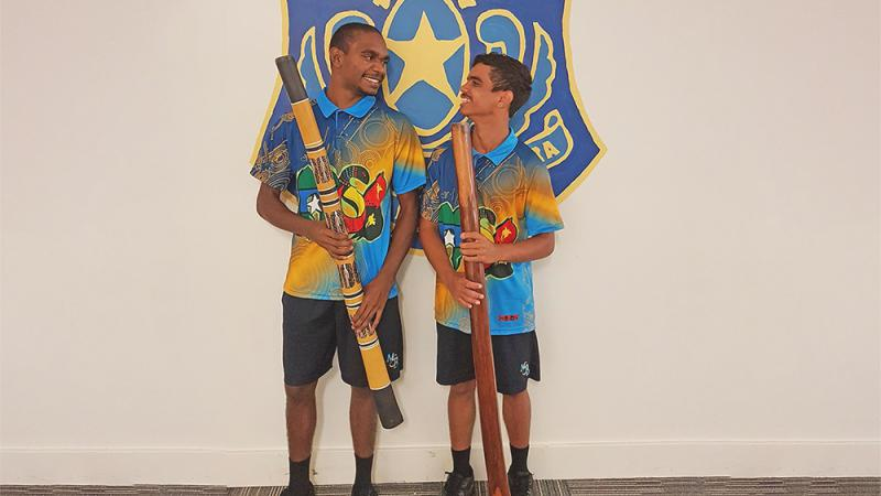 Two Aboriginal young men, wearing colourful shirts, hold didgeridoos as they stand beneath a blue and gold sign which includes a coat of arms.