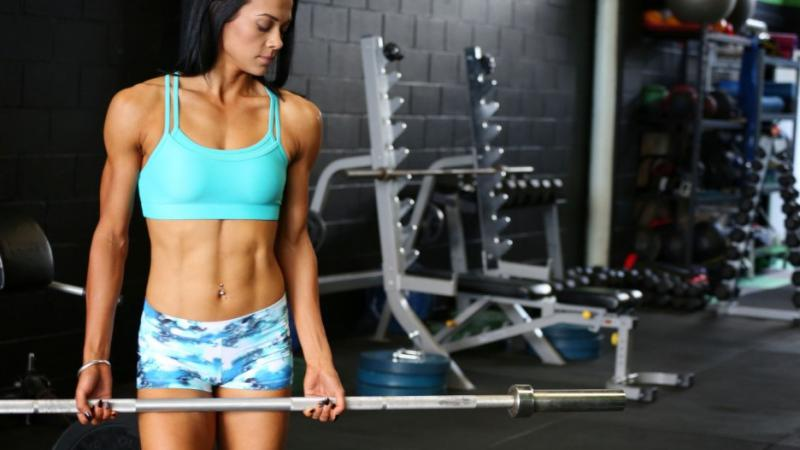 An Aboriginal woman dressed in bright aqua and white workout clothing holds a workout weight bar inside a gym with weights and equipment behind her.