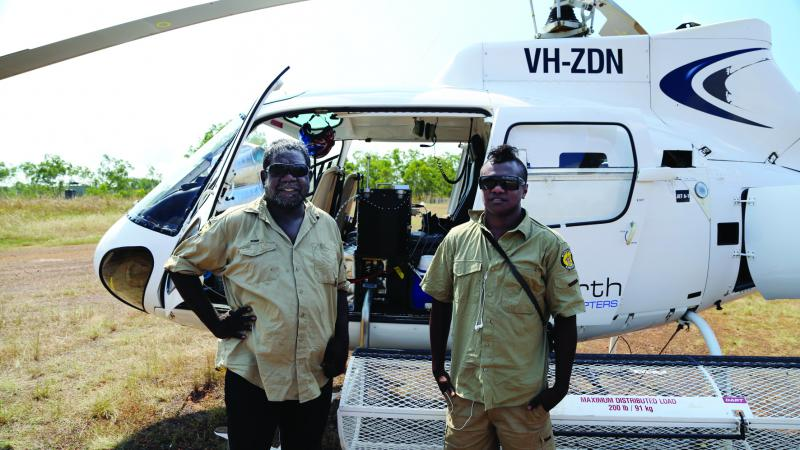 Two indigenous men standing in front of a helicopter