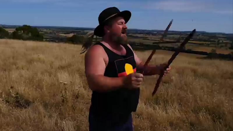 An Aboriginal man in black hat and black singlet with Aboriginal flag on it holds two sticks as he stands on a hill covered in dry grass. In the background is a blue sky, more hills and fields and trees.