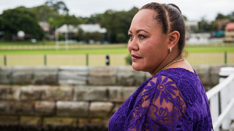 Indigenous woman with hair pulled back wearing a purple dress. In the background is a wall, then a playing field and buildings.