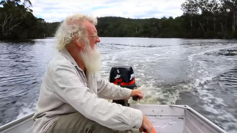 A white haired and white bearded man wearing a pale shirt sits in a boat with an outboard motor on a large river with trees in the background.