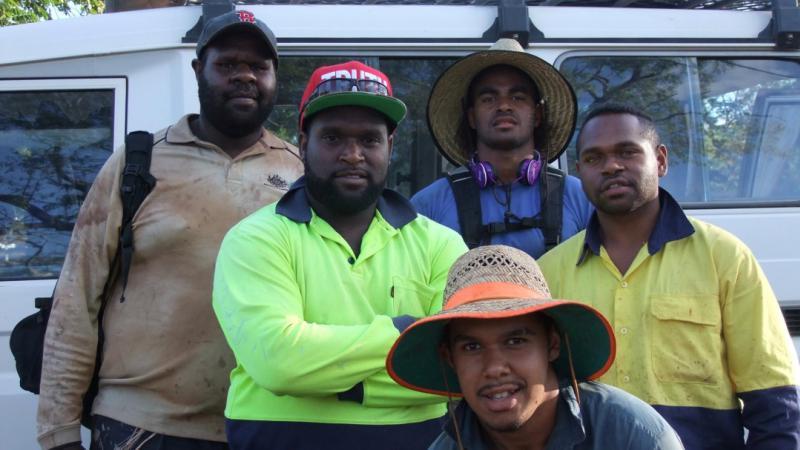 Five young Torres Strait Islander men standing in front of a mini-van smiling