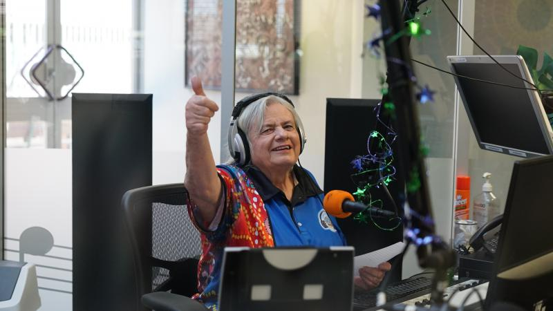Broadcaster Lorraine Rogers in the recording studio. She is looking at the camera giving the thumbs up.