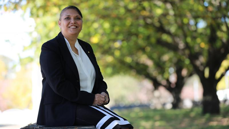 Indigenous woman in black jacket and white blouse sits in a wall in a park. In the background are trees and grass.