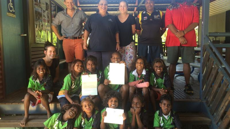 A group of Aboriginal school students sit on steps, holding a letter from the Prime Minister the Hon. Malcolm Turnbull, MP. Behind them stand five adults.