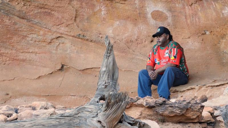 Aboriginal man in red shirt, blue jeans and a black cap sits on a rock ledge behind which are cave paintings. In front of him is a fallen log.