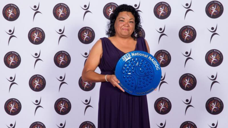 Indigenous woman Michelle Deshong holding blue plate shaped award.