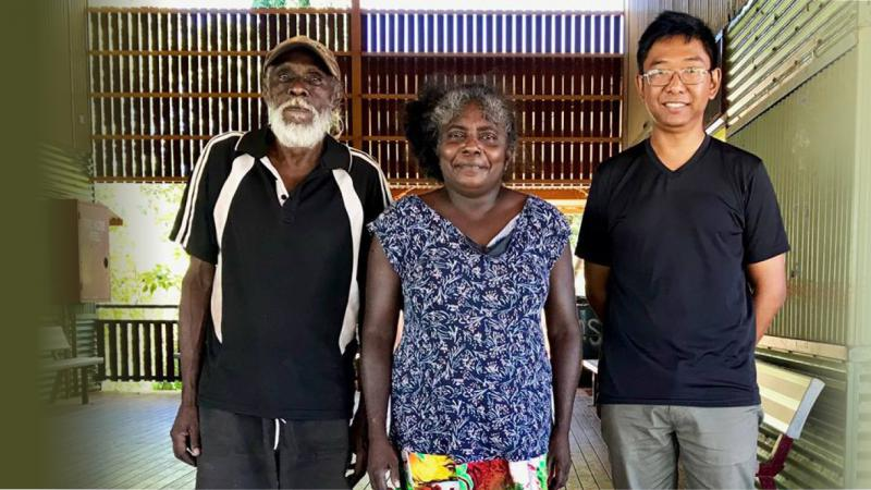 Three people stand on a wooden floor and behind them is a covered area with walls and ceiling but opened to the outside. An Aboriginal man in dark shirt and shorts is at left. Next to him is an Aboriginal woman in blue shirt and colourful skirt. At her le
