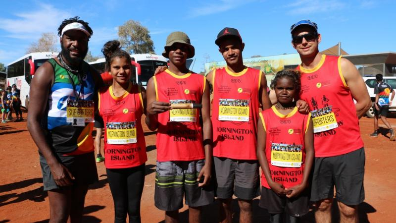 Six young athletes stand in the red dirt of central Australia.