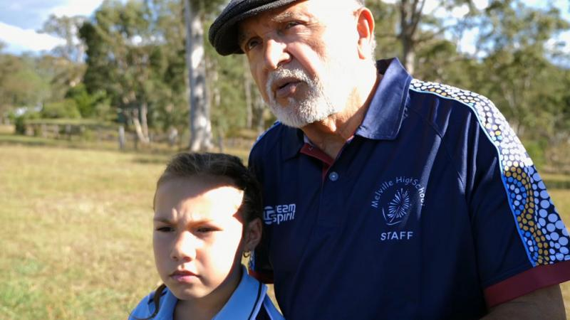 Elderly Aboriginal man in blue polo shirt with Aboriginal designs on the sleeves and wearing a cap stands with a young girls in a blue shirt. In the background is grass and trees.
