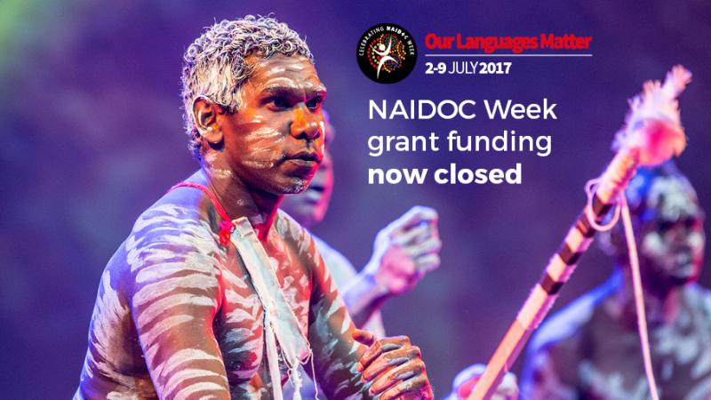 Three Indigenous men covered in traditional paint doing a traditional dance. The following words are shown: NAIDOC Week grant funding now closed.