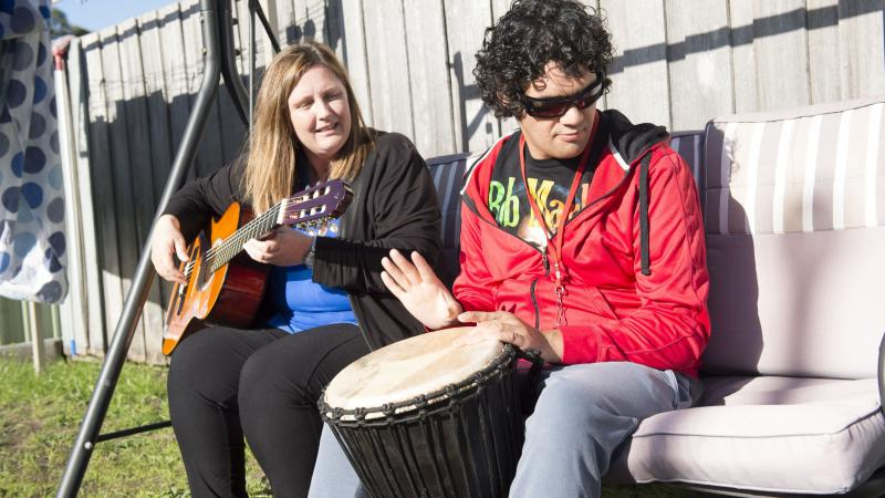 Seated on a large swing chair, an Indigenous woman dressed in black plays a guitar while an Indigenous man in red top and grey pants plays a large bongo drum.