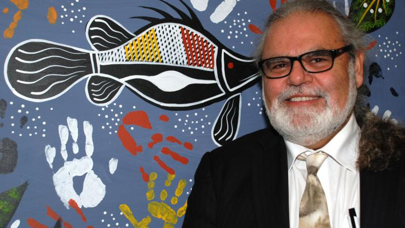 Founder & CEO of Nallawilli Technology, Roderick McLeod, stands in front of an indigenous painting