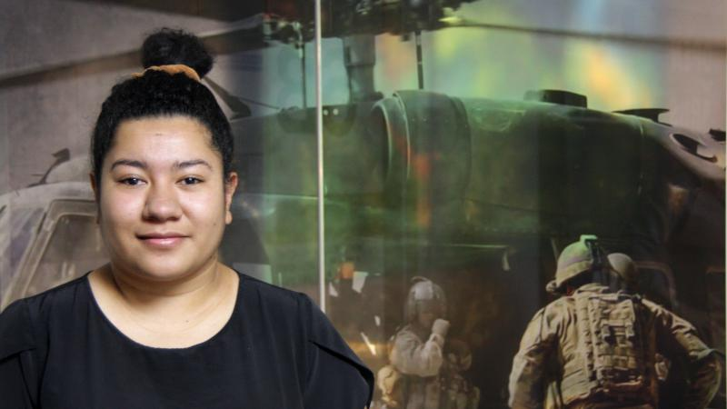 A woman wearing a black shirt with her hair in a knot. In the background is the image of a helicopter with military personnel in front of it.