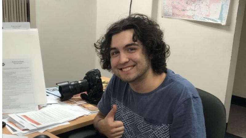 Young man with curly hair sits at an L-shaped desk. He wears a blue t-shirt. In the background are white walls, a map and a doorway. On the desk are papers, a camera, a computer keyboard and mouse.