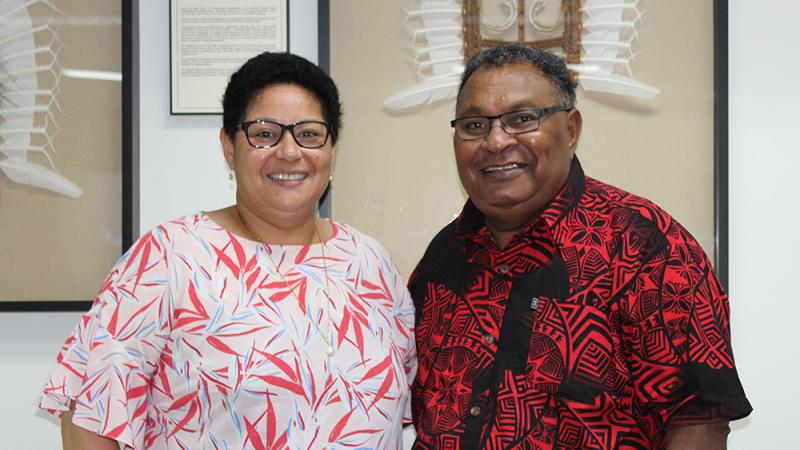 A woman in a pink floral shirt is standing next to a man in a red and black patterned shirt. Both the woman and man have short dark hair and black glasses.