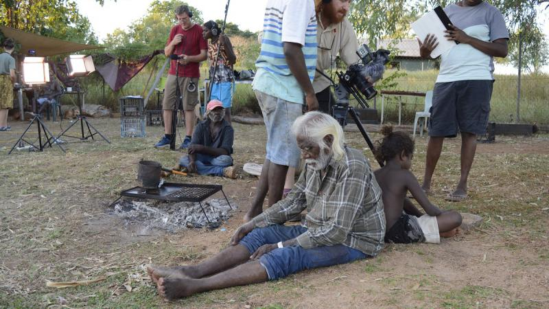 Elderly Aboriginal man sits back to back with young Aboriginal boy on grassy ground. Immediately behind them are three film-makers and further back are more Aboriginal and non-Aboriginal film makers another Aboriginal actor, lights, trees and grass.