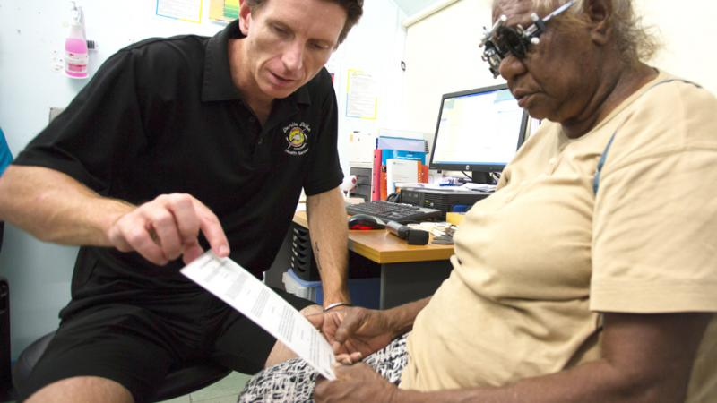 Optometrist Luke Arkapaw performing an eye check on an Indigenous woman