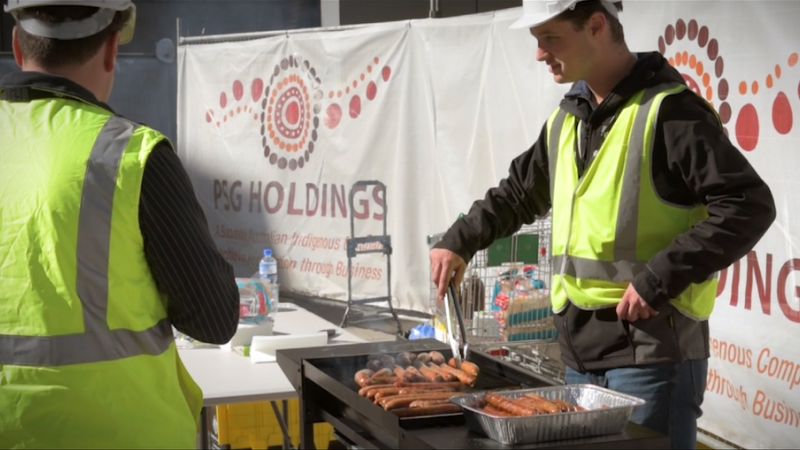Man in yellow high visibility vest and white hard hat turning sausages on BBQ in front of PSG Holdings site and a building site. 2nd man on right side in high vis vest with back turned.
