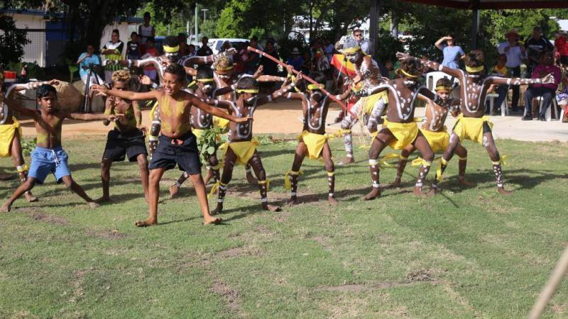 A group of Indigenous children with white ceremonial paint on their bodies wearing shorts or yellow coverings dance on green grass watched by a crowd of onlookers.