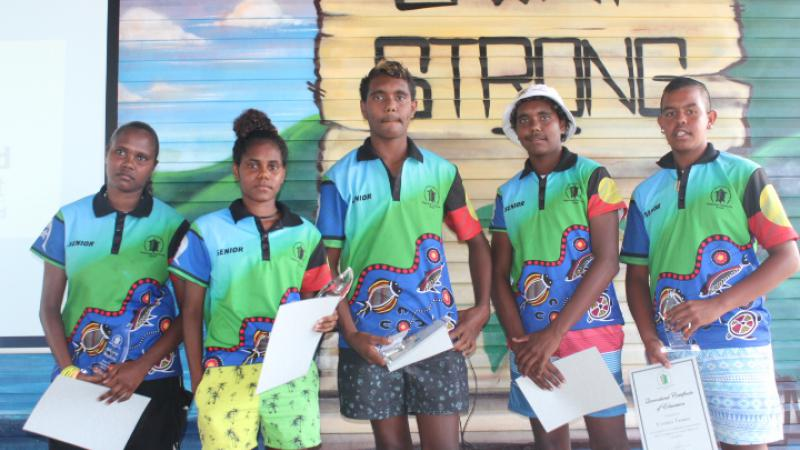Photo of 5 students in front of a mural on Palm Island