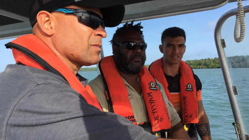 Three men in lifejackets stand in a boat with a roof over their heads. In the background is water and trees.