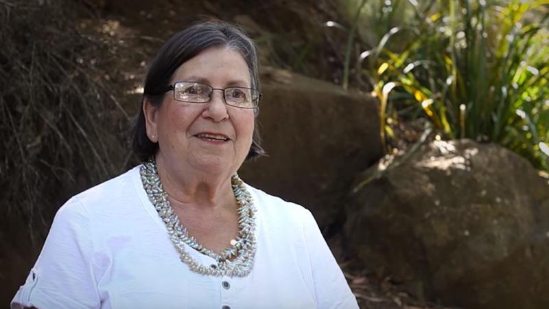 Elderly woman with dark hair wearing glasses, multiple necklaces and white dress stands in front of rocks and green foliage.