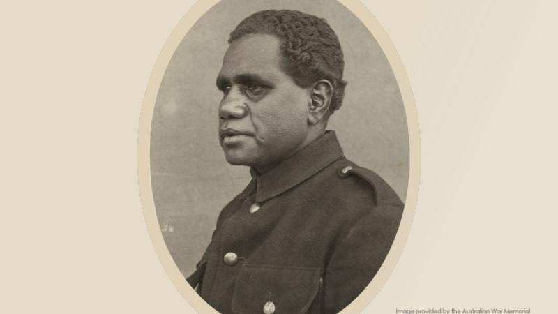 A portrait photo of an Indigenous man wearing a dark uniform buttoned up to the chin.