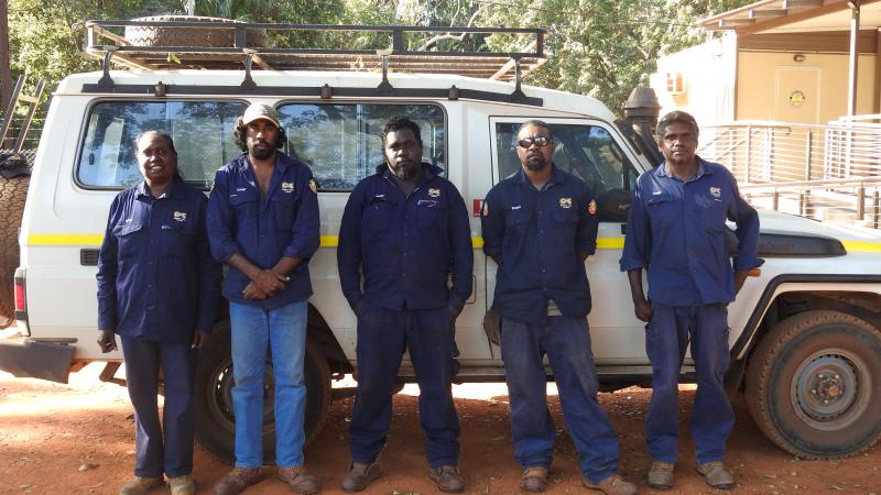 An Aboriginal woman and 4 Aboriginal men all dressed in blue ranger uniforms stand on red soil and in front of a white 4 wheel drive vehicle. In the background is a building and trees.