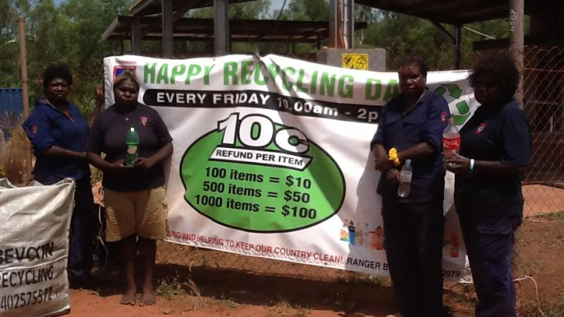 Four women rangers standing next to large green and white banner which says, happy recycling day.