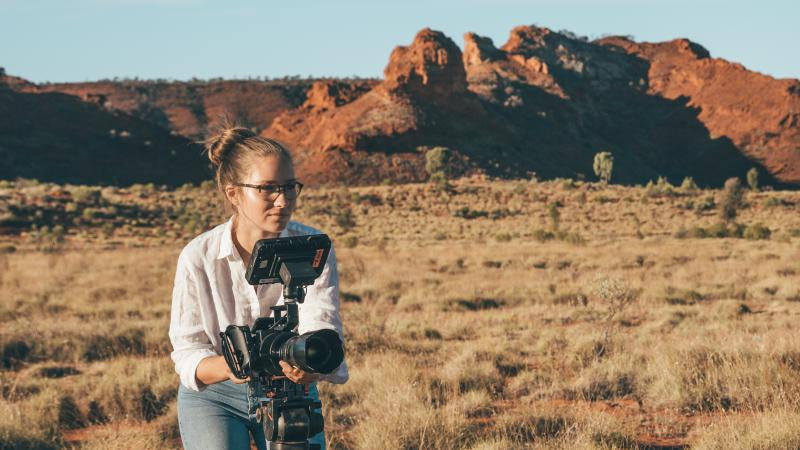 Young woman in white shirt and jeans holds camera. In the background is dry grass and a few trees. Further back is a small red and rocky hill beneath a blue sky.