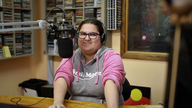 Aboriginal woman wearing glasses and a grey and pink top sits at a desk in front of a microphone. In the background is a rack of discs, a window and an Aboriginal flag.