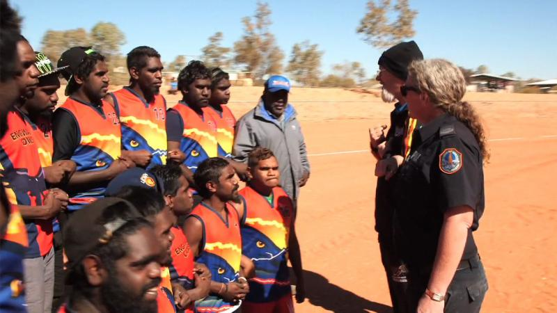 Group of Aboriginal footballers and others associated with the team on an ochre coloured football field.