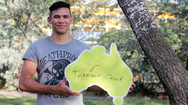 Young Indigenous man wearing grey t-shirt standing beneath a tree and holding a cardboard cut-out of Australia featuring a dot with an arrow to the words Tennant Creek.