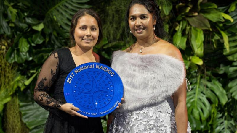 Two young Torres Strait Islander women standing with a background of plants. The young woman on the left is holding a large blue plate.