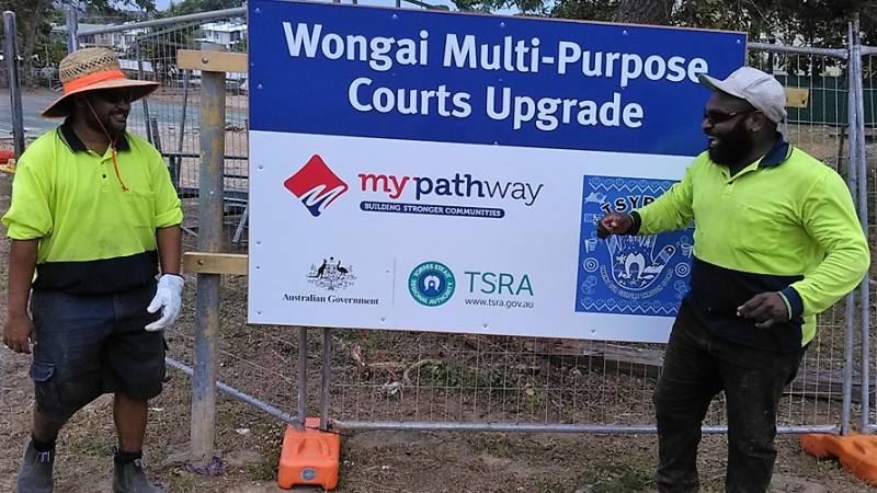 2 Indigenous men in workwear stand on dirt and in front of a wire barrier on which is a sign which says Wongai Multi-Purpose Courts upgrade.
