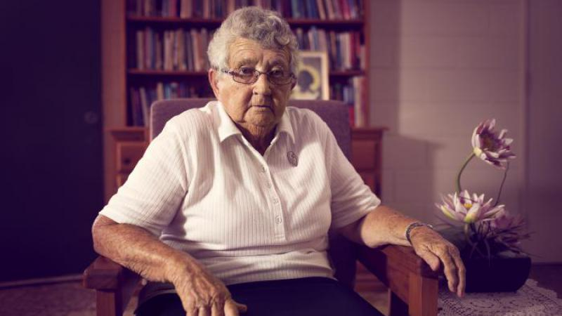 Photograph of an elderly woman wearing glasses and a white top, she is sitting on a wooden dining chair. Behind her is a bookshelf, and next to her is a plant.