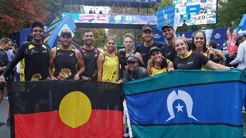 Group of Indigenous runners hold Aboriginal flag and Torres Strait Islander flag in front of them. Behind is a bridge and trees.