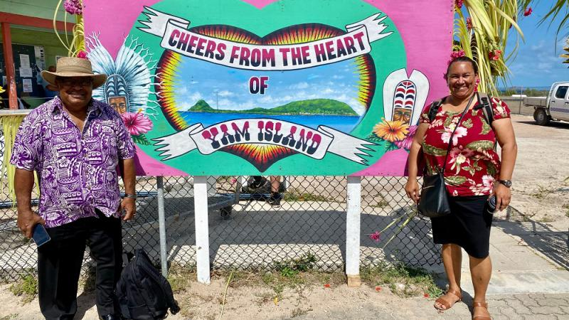 Indigenous man in brimmed hat, purple and white shirt and dark trousers and Indigenous woman in red flowery top and dark skirt stand either side of a large sign which says Cheers from the heart of Yam Island. In the background is a building and wire fence