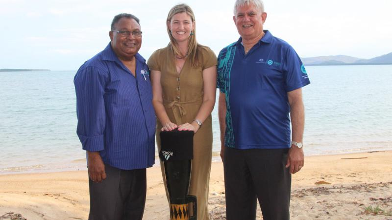 Two men in blue shirts and a woman in a brown dress, between them, stand on a beach. The woman supports a long black drum. In the background is water and land.