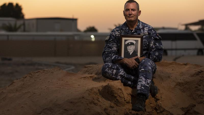 A man dressed in an air force uniform and holding a photo of another man in uniform sits on a dirt mound with a setting sun and buildings in the background.