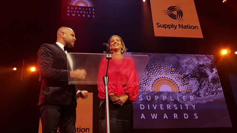 A man and a women stand at a lectern. Behind them is a sign with the Supply Nation logo and another sign with the text Supplier Diversity Awards.