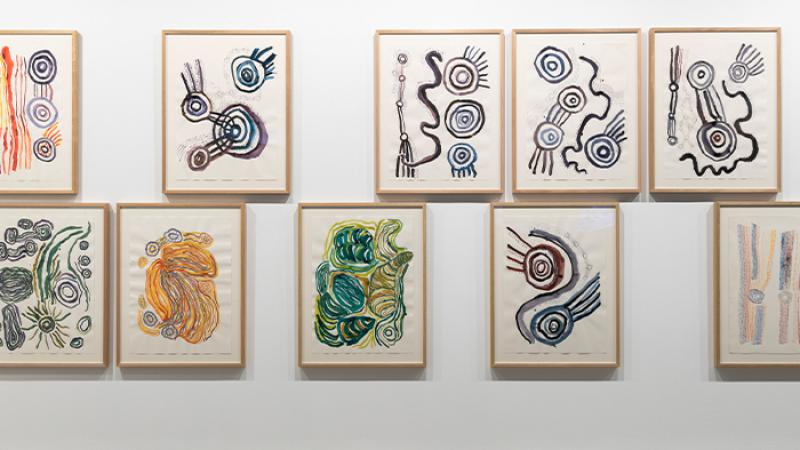 White wall on which is hung several framed paintings of swirling lines and circles and other Indigenous forms.