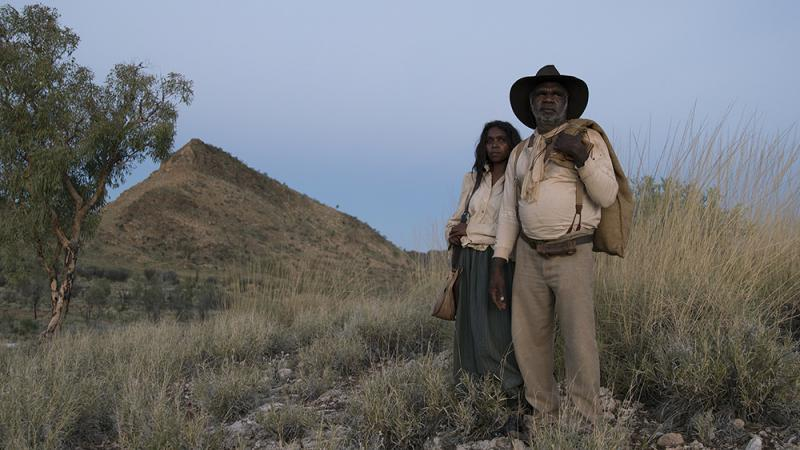 Aboriginal man and woman dressed in 1800s clothing stand on a rock and grassy hill. In the background are trees, a mountain peak and blue sky.